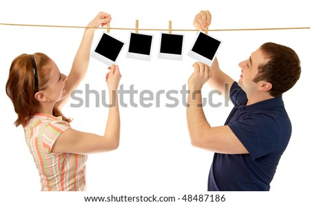 Young happy couple hanging blank photos over isolated white background