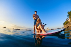 Young happy couple have fun on stand up paddleboard. Active paddle boarder paddling by sunset sea. Healthy lifestyle. Water sport, SUP surfing tour in adventure camp on family summer beach vacation