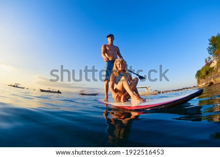 Young happy couple have fun on stand up paddleboard. Active paddle boarder paddling by sunset sea. Healthy lifestyle. Water sport, SUP surfing tour in adventure camp on family summer beach vacation Stock photo ©