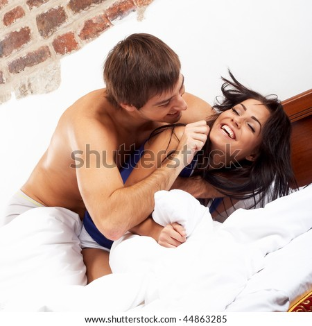 Young happy couple having a pillow fight in a bed