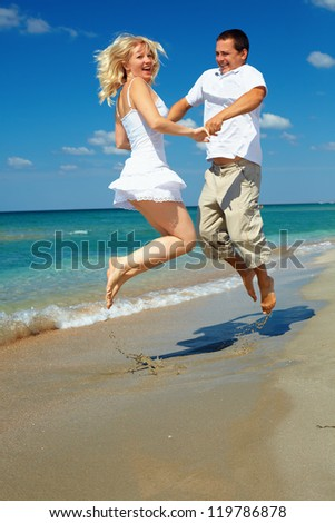young happy couple having fun on sea beach
