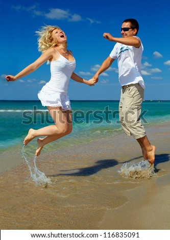 young happy couple having fun on sea beach. Black sea, Crimea