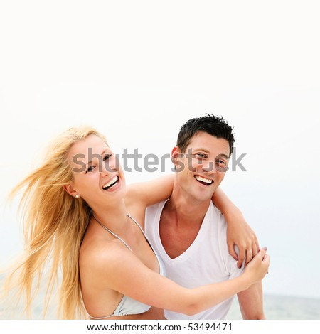 Young happy couple having fun on the beach. Shallow DoF with focus on the man.