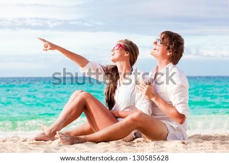 young happy couple having fun on tropical beach. honeymoon