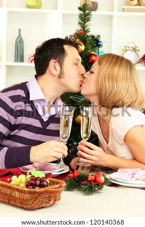 Young happy couple holding glasses with champagne at table near Christmas tree