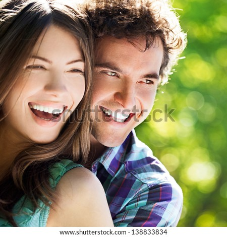 Young happy couple hugging and laughing.