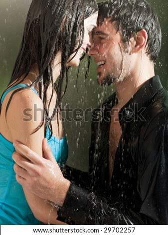 Young happy couple hugging under a rain