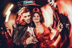 Young Happy Couple in Costumes at Halloween Party. Handsome Man and Beautiful Woman Drinking Champagne at Halloween Party in Nightclub. Friends having Fun. Celebration of Halloween