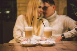 Young happy couple in love in cafe, man and woman together smile hugging, drinking coffee. Couple Talking In Cafe In Winter. Happy couple enjoying a coffee at the coffee shop. Happiness, christmas.