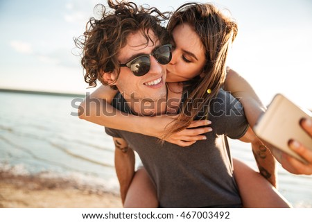 Young happy couple in love kissing and making selfie at the beach, piggyback ride