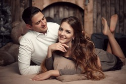 Young happy couple in love lying on rug in cozy wooden interior. Beautiful brunette woman with boyfriend enjoying.