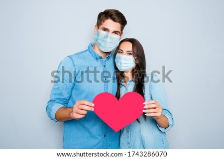 Young happy couple in love story photo shoot holding red paper heart wear medical safety sterile mask on face, social distance pandemic corona virus prevention protection concept covid 19