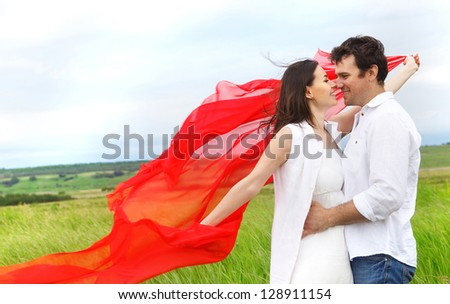 Young happy couple in love with red fabric in summer day. Outdoors portrait