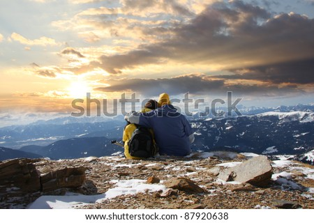 Young happy couple in snowy mountains against sunset