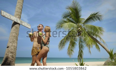 Young happy couple in swimwear drinking coconut milk, enjoying sunny summer day on their beach tropical holiday #1055803862