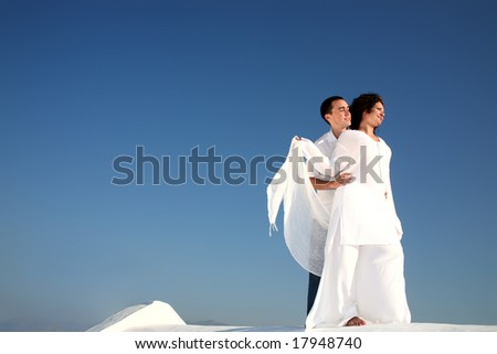 young happy couple in white over a blue sky background