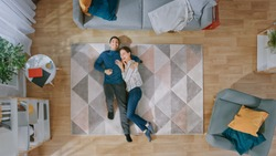 Young Happy Couple is Lying Down on the Floor and Laughing. Man Hugs the Girl. Cozy Living Room with Modern Interior with Carpet, Sofa, Chair, Table, Shelf, Plants and Wooden Floor. Top Down.