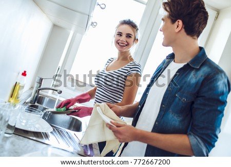 Young happy couple is washing dishes while doing cleaning at home.