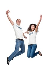 Young happy couple jumping up isolated on white