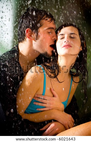 romantic couple kissing in the rain. Young happy couple kissing