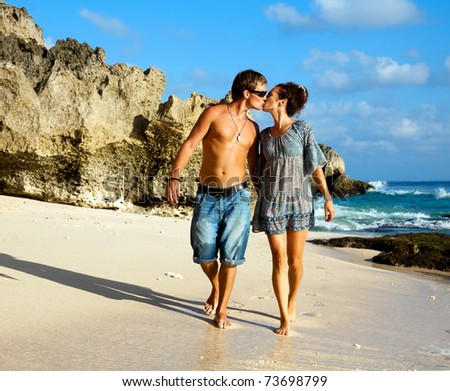 Young happy couple kissing during a walk along the coast