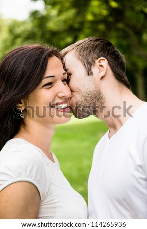 Young happy couple kissing  - outdoor lifestyle portrait