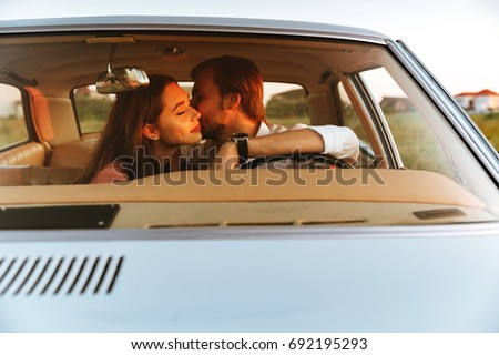 Young happy couple kissing while sitting together inside a car. Front window view