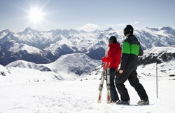 Young happy couple looking in snowy mountains holding ski