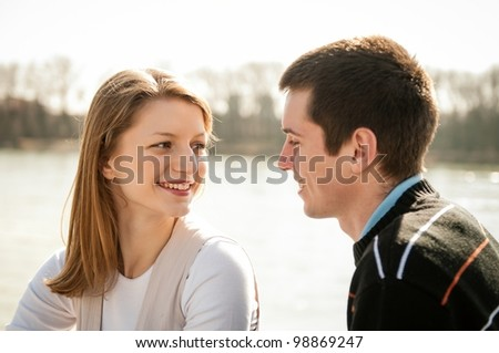 Young happy couple looking on each other  - outdoor lifestyle portrait