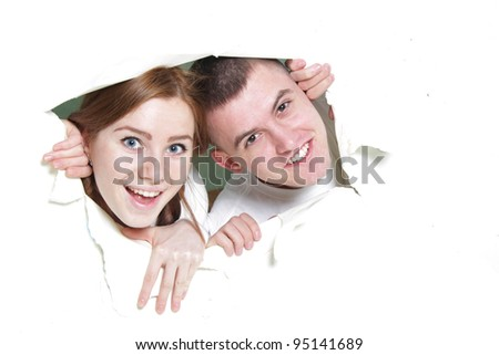 young happy couple looking out from hole in paper