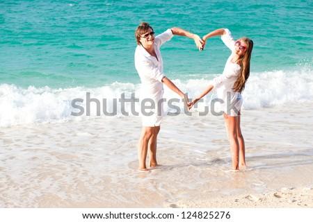 young happy couple making heart shape on tropical beach. honeymoon - stock photo
