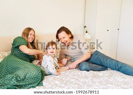 Young happy couple mother and father playing with adorable toddler 1 year old girl, family relaxing in bed