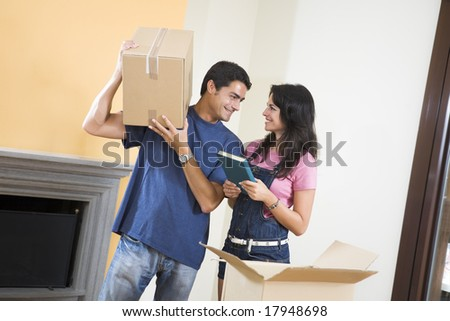 Young happy couple moving boxes at home