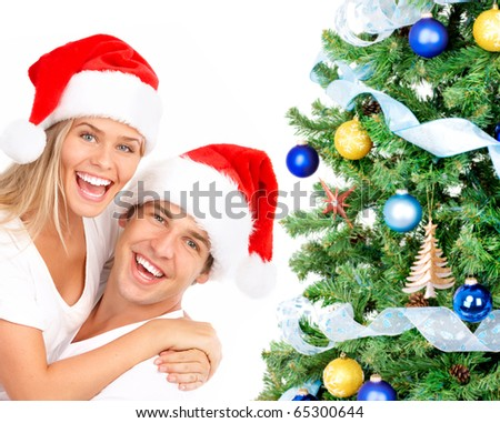 Young happy couple near  a Christmas tree. Isolated over white background
