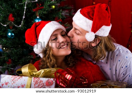 Young happy couple near a Christmas tree with presents