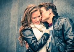 Young happy couple of lovers at beginning of love story - Handsome man whispers soft kisses in beautiful woman ear - Fall fashion concept with boyfriend and girlfriend on a cold vintage filtered look