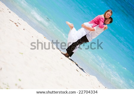 Young happy couple on white sand beach