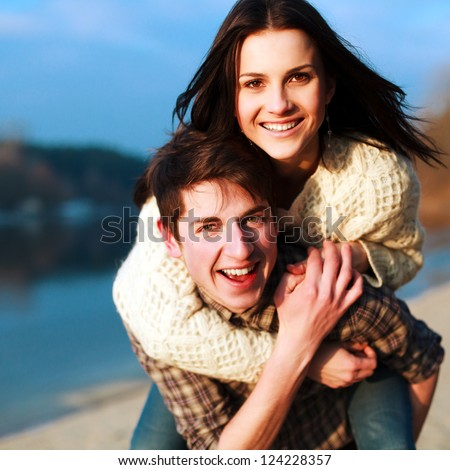 Young happy couple outdoor portrait. Beautiful boy and girl have fun on the beach.
