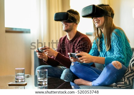Young happy couple playing video games virtual reality glasses in their apartment - Cheerful people having fun with new trends technology - Gaming concept - Focus on woman headset