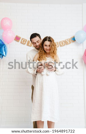 Young happy couple posing with baby shoes during gender reveal party indoors Photo stock ©