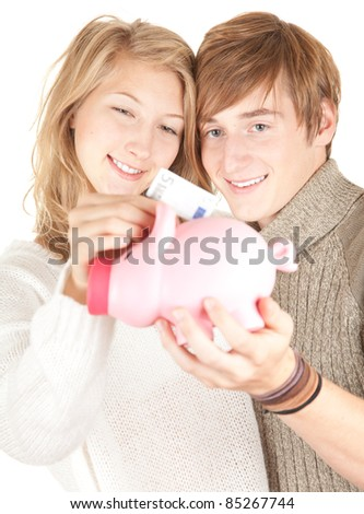 young happy couple putting five euro in piggy bank