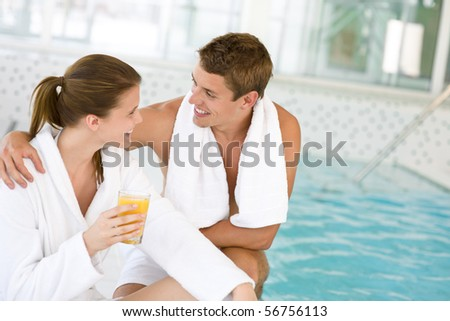 Young happy couple relax at swimming pool, drink juice