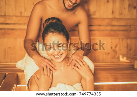 Young happy couple relaxing inside a sauna at spa resort hotel luxury - Romantic lovers having a bodycare day in steam bath man making a massage for his girlfriend - Relax, love, lifestyle concept #749774335