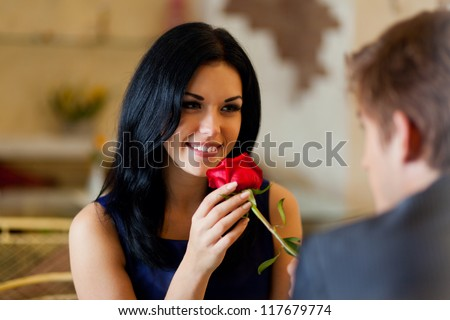 Young happy couple romantic date at restaurant, celebrating valentine day man give red rose to his girl