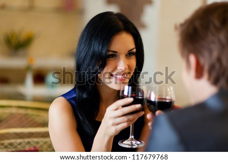 Young happy couple romantic date drink glass of red wine at restaurant celebrating valentine day