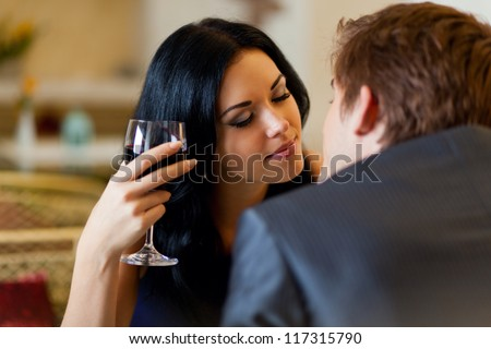 Young happy couple romantic kissing date with glass of red wine at restaurant, celebrating valentine day kiss