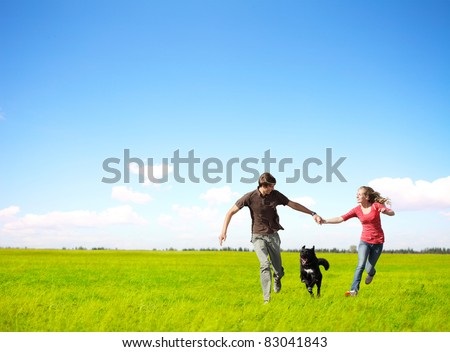 Young happy couple running on a green meadow with a dog