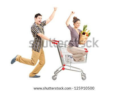 Young happy couple shopping, man pushing a shopping cart isolated on white background