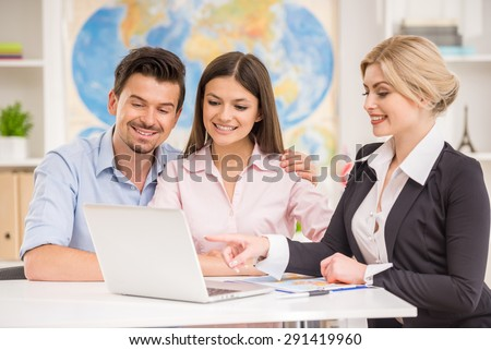 Young happy couple sitting at tourist agency and talking with travel agent.