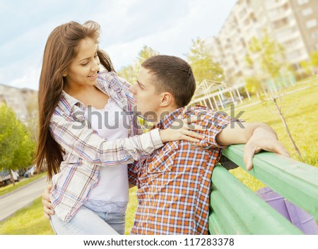 young happy couple sitting on green bench. - stock photo